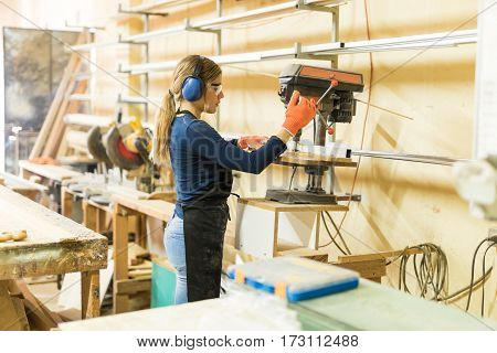 Female Carpenter Using A Drill Press