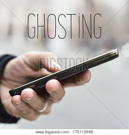 closeup of a young caucasian man using a smartphone in the street and the word ghosting
