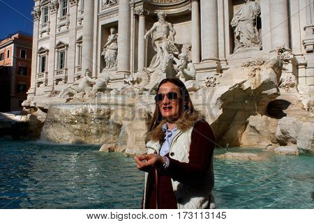Throwing a coin in famous Trevi Fountain in Rome Italy.