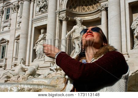 Girl throwing coin in famous Trevi Fountain in Rome Italy.