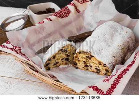 Christmas stollen powdered with cut off piece with knife in wicker basket ingredients kitchen towel top view rustic interior