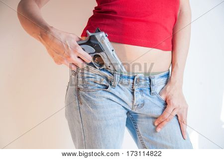 Detail Of Pistol Holding In Jeans Waist Ofyoung Woman