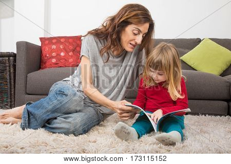 Little Child And Mother Reading A Tale Book At Home