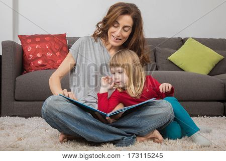 Mom And Little Child Reading A Tale Book At Home