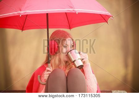 Nature outdoor weather fun cozy concept. Girl sitting in park. Lady sovering herself from rain by holding umbrella drinking coffee from cup while staying on bench.