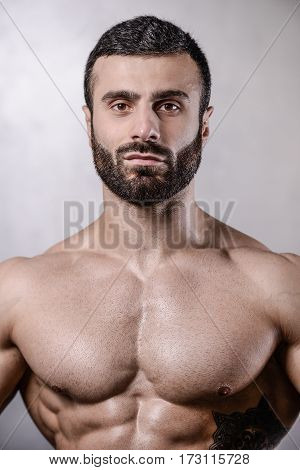 Brutal Strong Bodybuilder Man Posing In Studio On Grey Background.