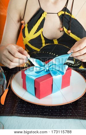 woman with brown and yellow dress opening blue bow of gift red present box with hands over white dish in table of restaurant