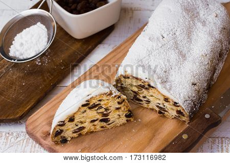 Powdered Christmas stollen with cut off slice on wood board ingredients sieve with icing sugar knife rustic kitchen interior