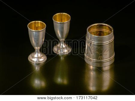 On a black background-three silver cups gilt inside. Retro noble form.