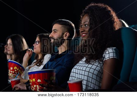 Movie buddies. Portrait of a multicultural group of friends enjoying movies together at the cinema