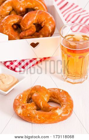 Bavarian pretzels with mustard on cutting board.