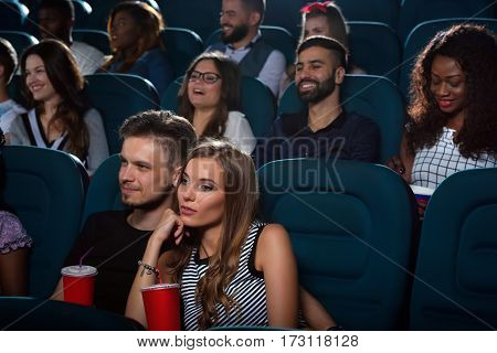 His favorite company for movies. Young handsome man smiling embracing his beautiful girlfriend while watching a movie together at the movie theatre