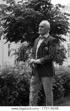 Elegantly dressed old man standing outdoors near the apartment buildings alone. Black and white.