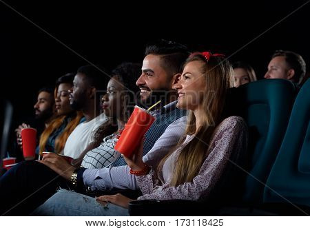 Ready to rate a new movie. Shot of multicultural cheerful friends watching a movie together at the local cinema