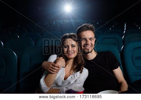Romantic moments at the cinema. Shot of a young lovely couple smiling cheerfully enjoying a movie at the cinema