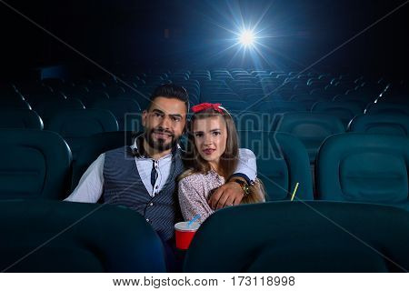 First date going well. Beautiful young couple embracing while watching a movie in an empty cinema hall copyspace