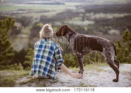 Woman and her dog posing outdoor. Girl loving and touching her dog paws and watching landscape.