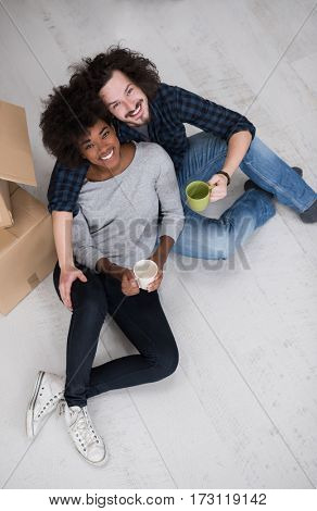 Relaxing in new house. Cheerful young multiethnic couple sitting on the floor and drinking coffee while cardboard boxes laying all around them