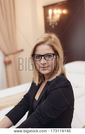 Young entrepreneur woman looking at camera in elegant hotel room