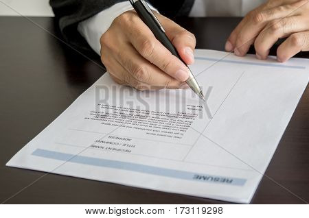 Businessman Or Job Seeker Signing On Resume Form.