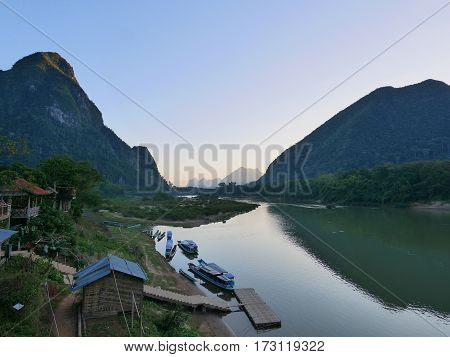 Jetty asian long tail boats and a river in a beautiful hill mountain landscape