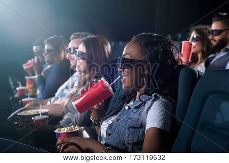 All you need for a perfect movie night. Attractive young African female smiling joyfully holding her coke and popcorn watching a movie at the cinema