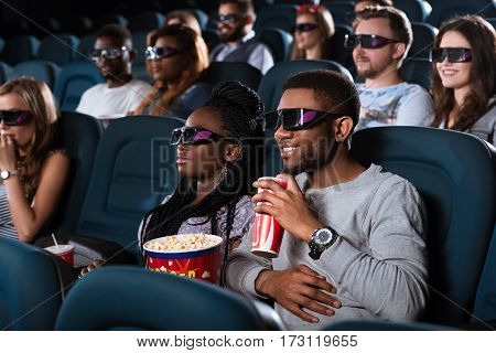 Fantasy brought into reality. Portrait of a handsome cheerful African man smiling while watching a 3D movie with his girlfriend at the movie theatre