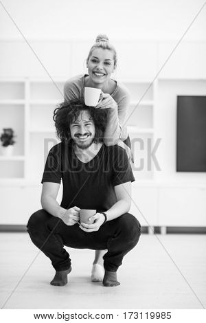 Portrait of a happy young beautiful couple hugging and drinking coffee in their new home
