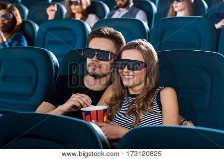 Good times together. Portrait of a young loving couple hugging on a date at the 3D movie theatre