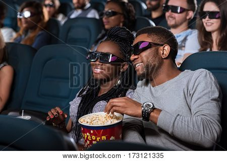 Spectacular film. Closeup portrait of an attractive young African couple smiling happily while watching a movie at the cinema