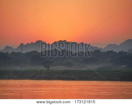 Sunset orange sky over calm steady wide river