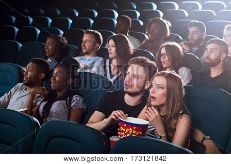Breathtaking film. Shot of a beautiful young couple looking shocked while watching a movie at the local cinema together