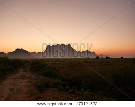 Silhouette of mount zwegabin in Hpa-an Myanmar during morning sunrise with a small path on the left leading into fields close to the mountain