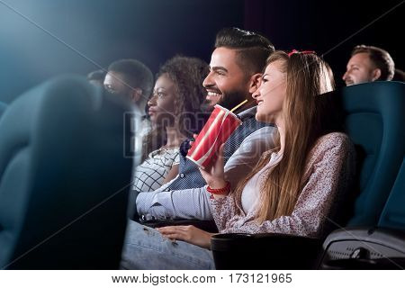 This movie is a hit Shot of a beautiful female holding her coke smiling cheerfully enjoying a movie with her friends at the local cinema
