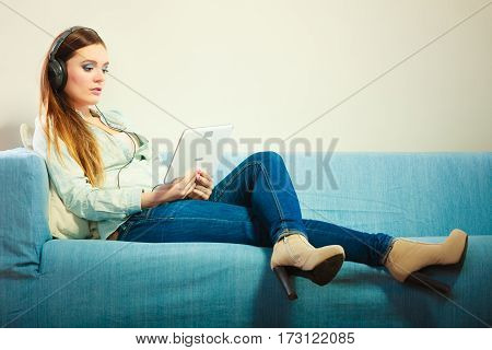 Modern technologies leisure and lifestyle concept. Young attractive woman with headphones sitting on couch using tablet