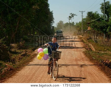 04 february 2017, hpa-an, myanmar - smiling young asian boy on his bicycle driving on a dirt road with balloons in his hand