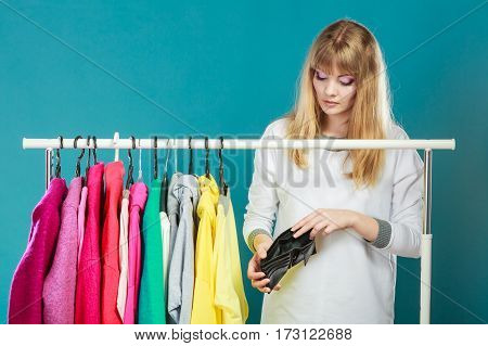 Pretty woman looking into empty wallet wants clothing from wardrobe. Young undecided shopper girl spend all money for clothes. Shopaholic concept.