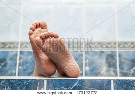 Wrinkled Bare Feet Coming Out From A Bathtub. Young Person Getting A Bath Feet Close-up Indoor In Ba