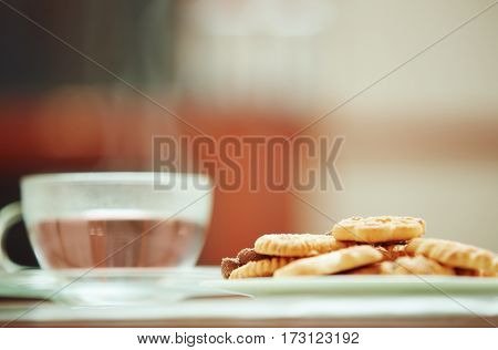 Cup of water and cookies. Close-up horizontal photo