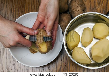 Detail Of Woman Hands Peeling Fresh Yellow Potato With Kitchen Knife, Food Preparation Concept.