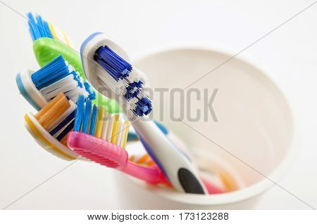 Close up shot of set of multicolored toothbrushes in glass on clean toilet on white background concept dental.