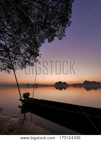 Back of a long tail boat on a river side and tree leaves in front of an amazing colorful orange blue yellow calm and tranquil sunset without direct sunlight