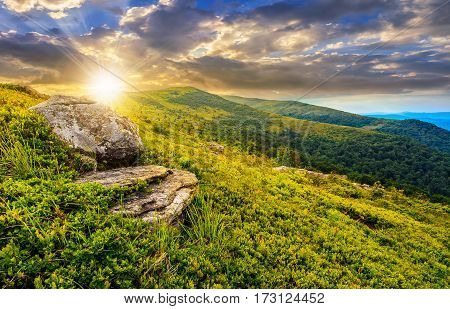 grassy meadow with giant boulders on the of a hill in Carpathian mountain ridge at dramatic sunset under cloudy sky. Beautiful summer landscape