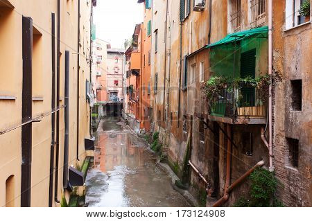 Old water canal hidden behind a window in Bologna Italy