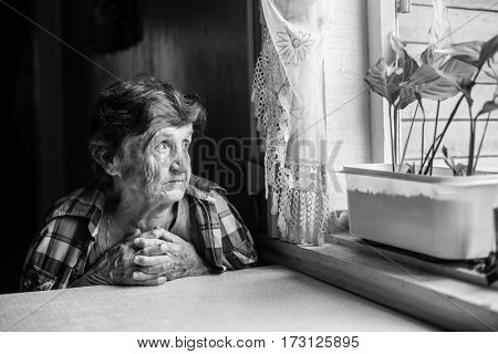 An elderly lady sits sadly near the window of his old house. Black-and-white photo.