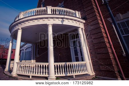 Round white two story  wooden porch with pillars