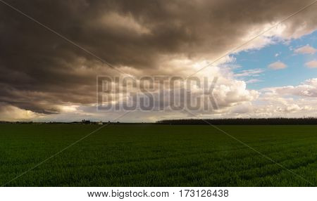 Open field as clouded skies leave a storm passes by.
