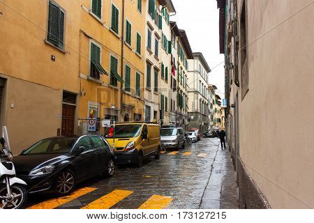 FLORENCE ITALY - FEBRUARY 06 2017: Old streets in Florence with green shutters and a car after rain