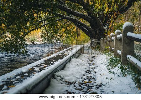 Image of a snow covered path by a river.