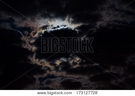 The night is dark gloomy sky. The moon shines through the clouds. Full moon. Gothic night background. Night concept